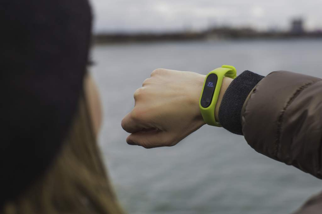 Woman looking at lime-green fitness tracker on her wrist.