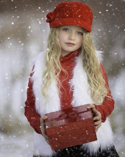 Little girl with long blonde hair wearing a red and white outfit and holding a red gift-wrapped present on a snowy day.