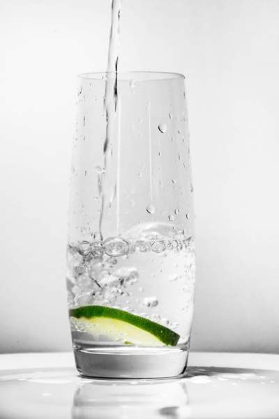 Water being poured into a glass with a slice of lime at the bottom.