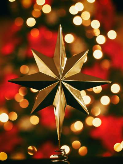 Gold star Christmas decoration against a red and gold background.