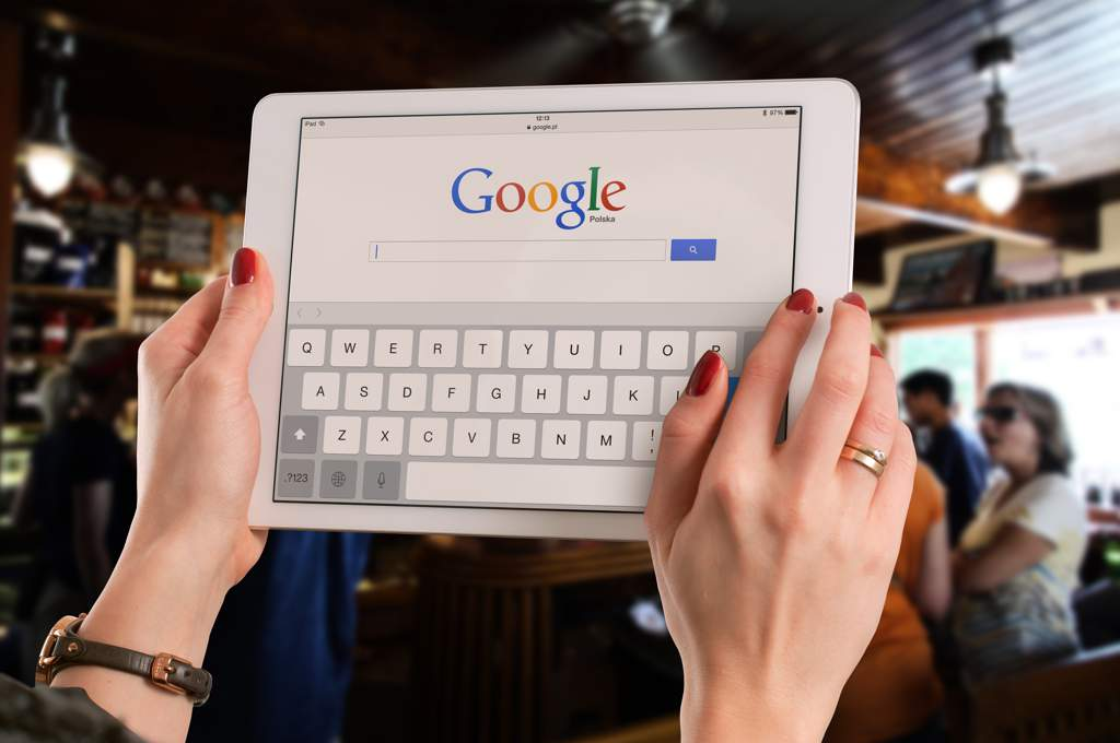 Woman's hands holding up a tablet computer in a restaurant or bar. There is a Google search screen on the tablet.