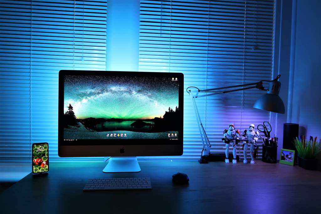 Desk with a monitor, lamp, phone and star-wars figurines in front of some slatted blinds. The whole scene is bathed in blue/green light.