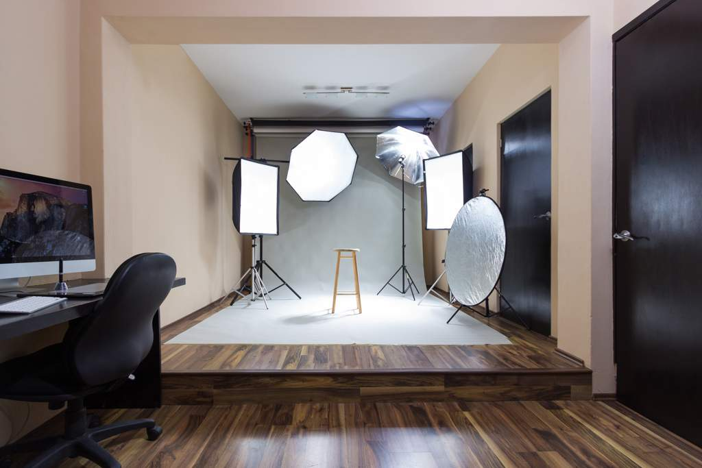 Office with wooden floor looking through to a photographic studio area with lights, reflectors and a photographic background.