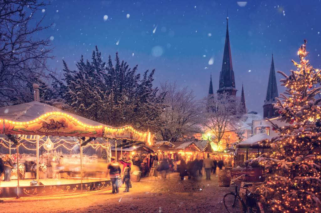 Traditional Christmas market in the snow with illuminated stalls, a church with a spire and a snow-covered christmas tree in the foreground.
