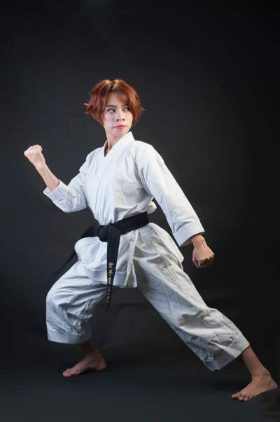 Woman with red hair wearing a karate outfit and a black belt doing karate.