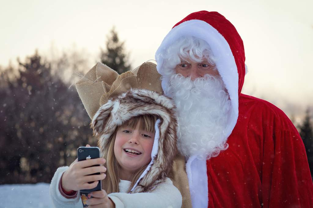 Girl wearing a furry hat takes a selfie with Santa Clause on a snowy day.