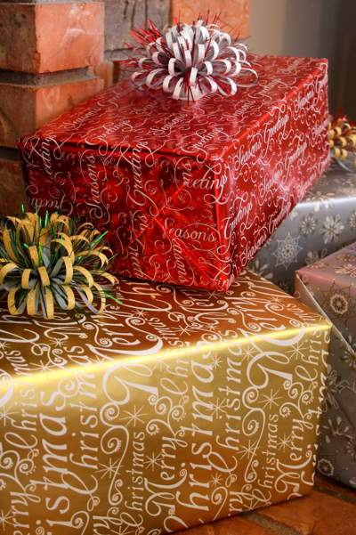 Gift-wrapped presents with fancy bows in red, gold and silver wrapping paper with Merry Christmas and Seasons Greetings designs.
