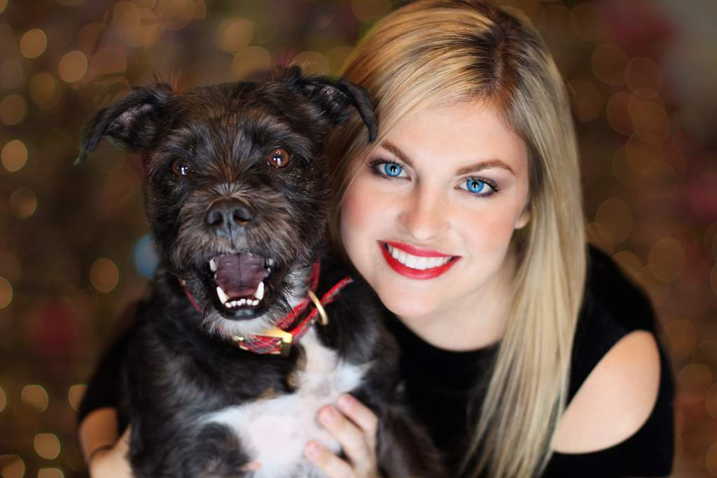 Young woman with blonde hair holding a black dog with a red tartan collar.