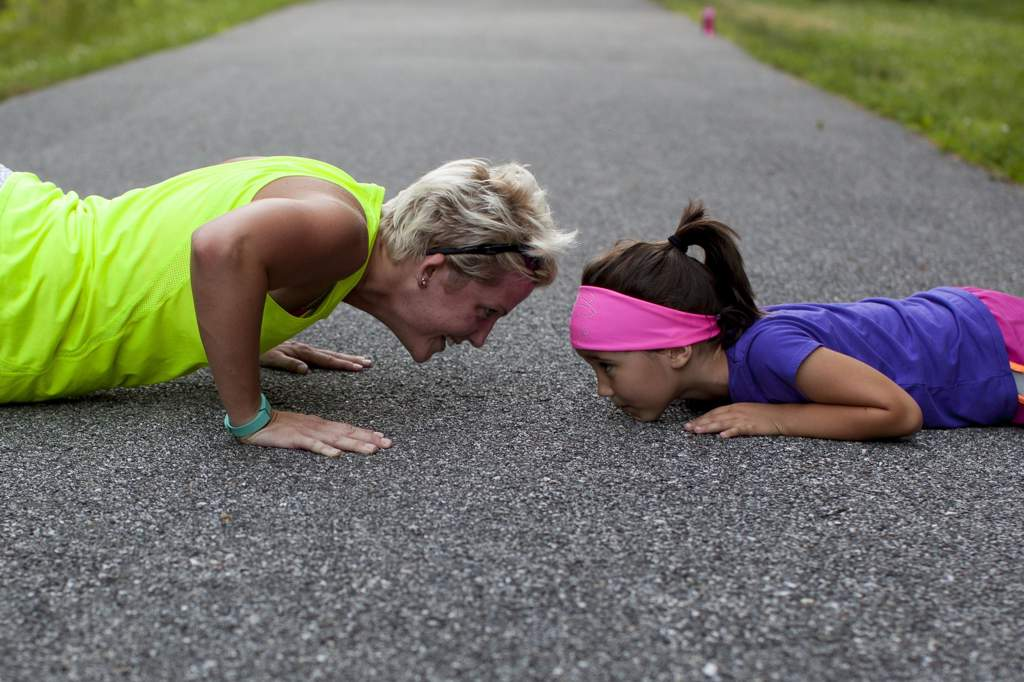 A woman in a flourescent green top and a young girl facing each other on a road, doing push-ups.