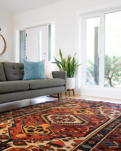 A patterned oriental rug in a white room with large windows, a grey sofa and houseplant.