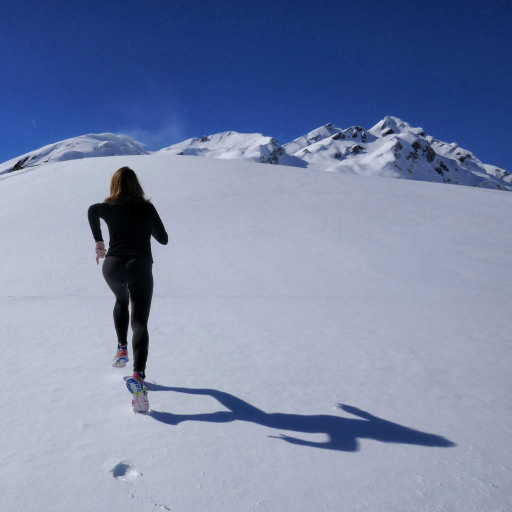 Woman wearing black running up a snowy slope towards some mountains underneath a blue sky.