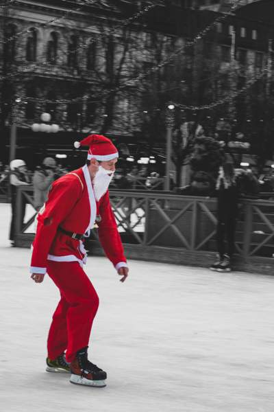 Man skating in a red and white Santa Clause costume.