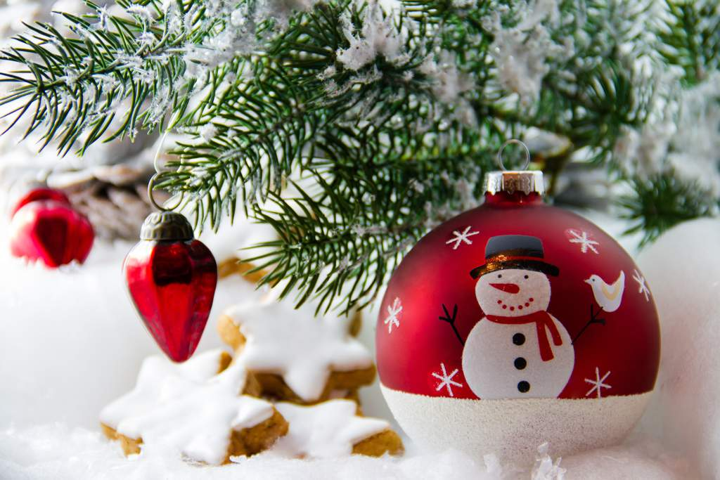 Branch of a Christmas tree with red decorations, a large red bauble with a snowman design and star-shaped biscuits with white icing, on a snowy white background.