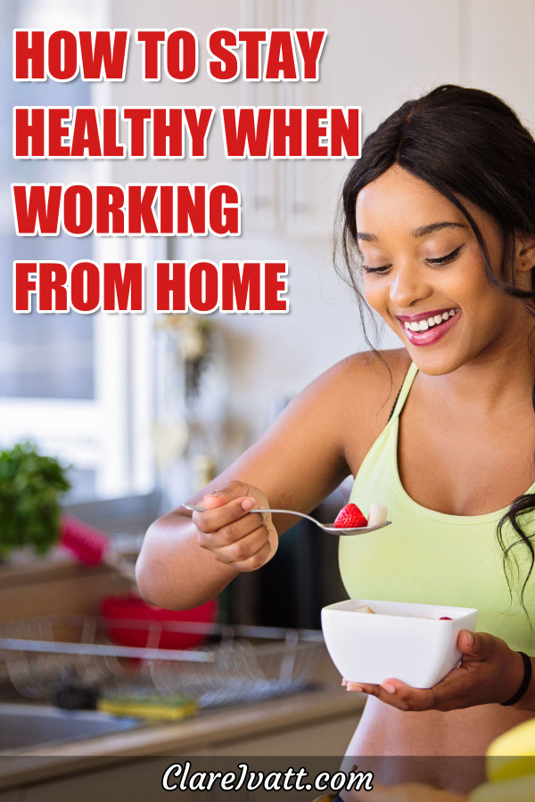 Young woman in workout clothes standing in a kitchen eating a healthy snack from a bowl.