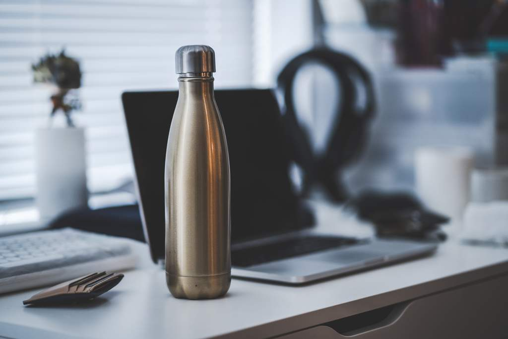A metal bottle or flask standing on a desk next to a laptop computer.
