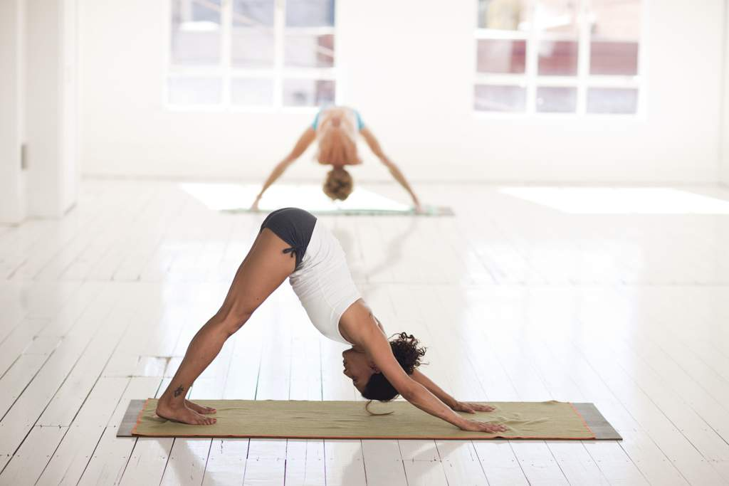 Two women doing yoga in a white room.