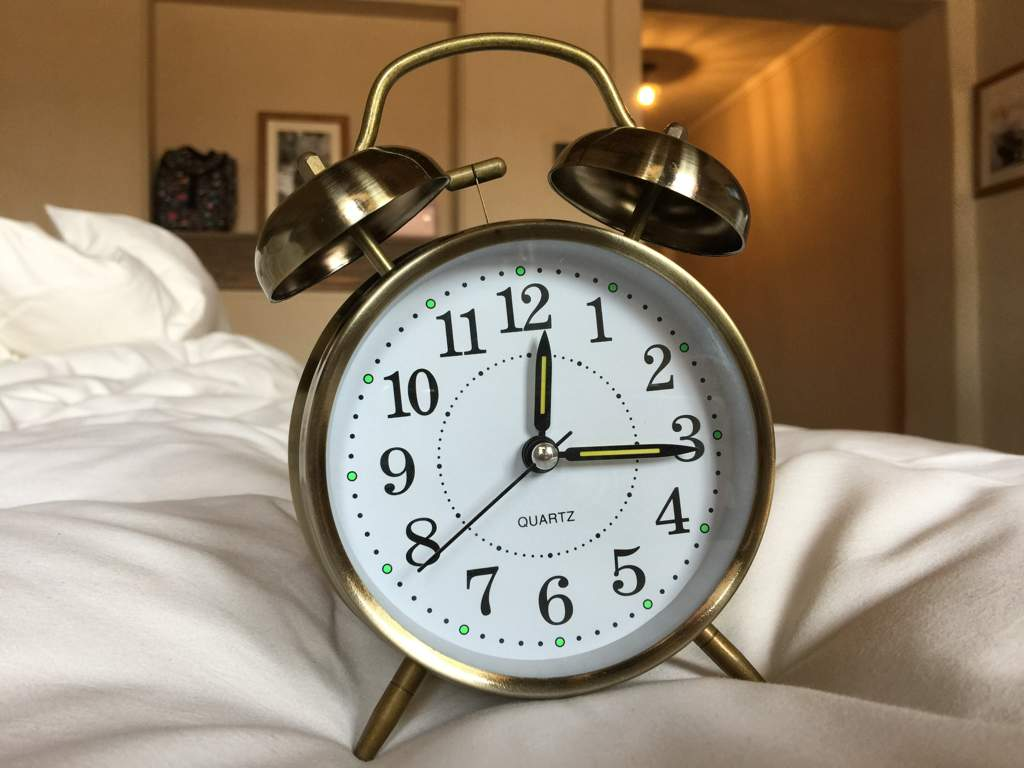 Brass alarm clock on a bed with white bedding.