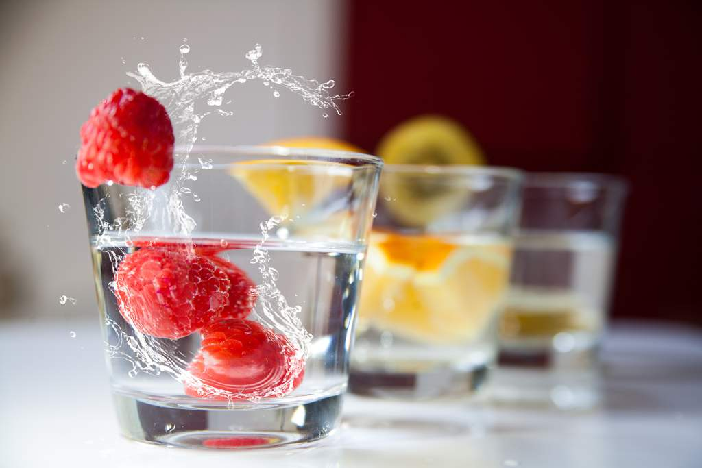 Three glasses of water with fruit - in the front glass, three raspberries have just been dropped into the glass splashing the water over the side.
