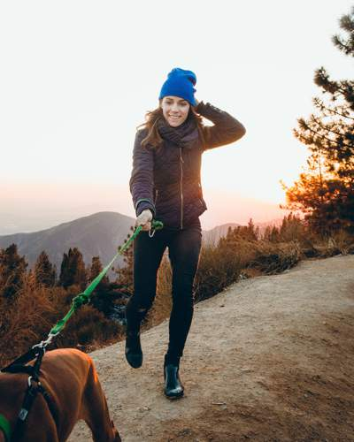 Woman wearing a brown jacket and a blue wooly hat being pulled along a path by a dog which is leaving the lower-right of the photograph. Thee are mountains and sunrise in the background.