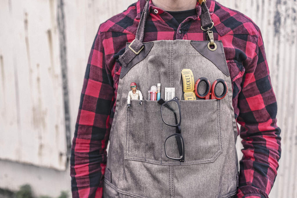 Close up of body of a man wearing work style dungarees with random objects in front pocket, and a checked red shirt