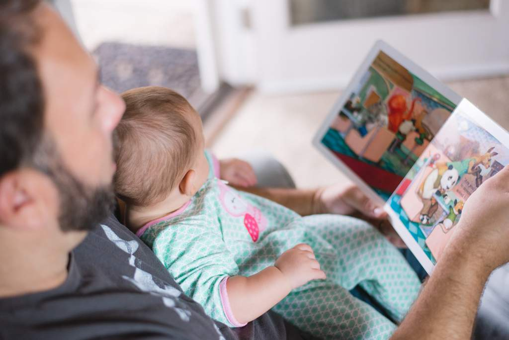 Father reading a book to a baby sitting on his lap