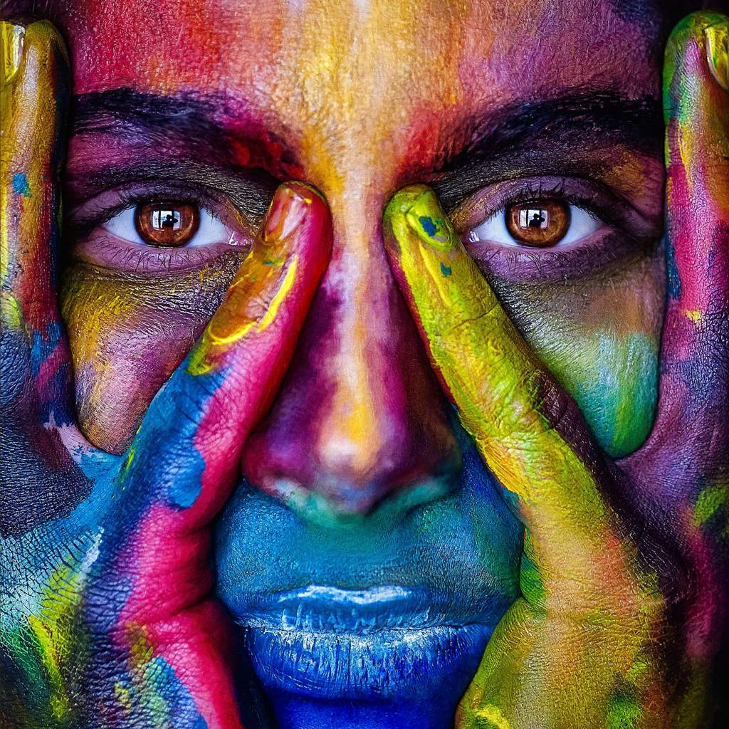 Closeup of girl's face resting in her hands, covered in multi-coloured paint