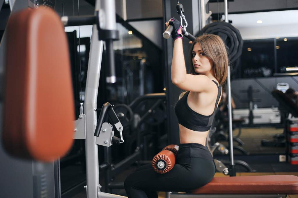 Woman wearing black gym-wear using a pull-down exercise machine in a gym.