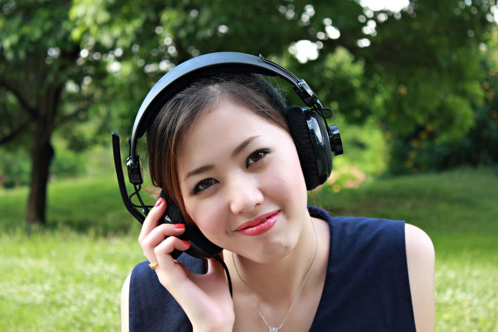 Woman in a park wearing headphones.