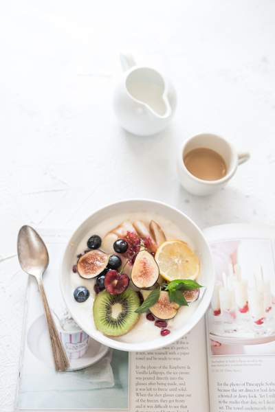 White bowl containing healthy breakfast of fruits and yoghurt. There is a cup of tea and a jug of milk and a spoon on the table.