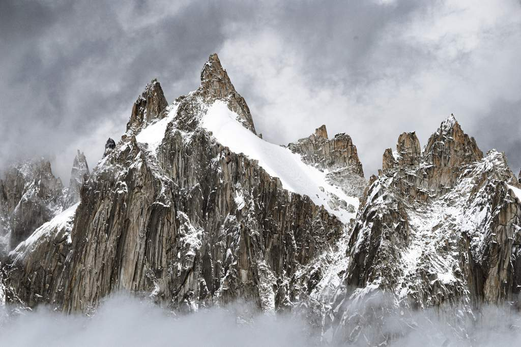 Dramatic mountain landscape with snow covering some of the rocks, and low clouds