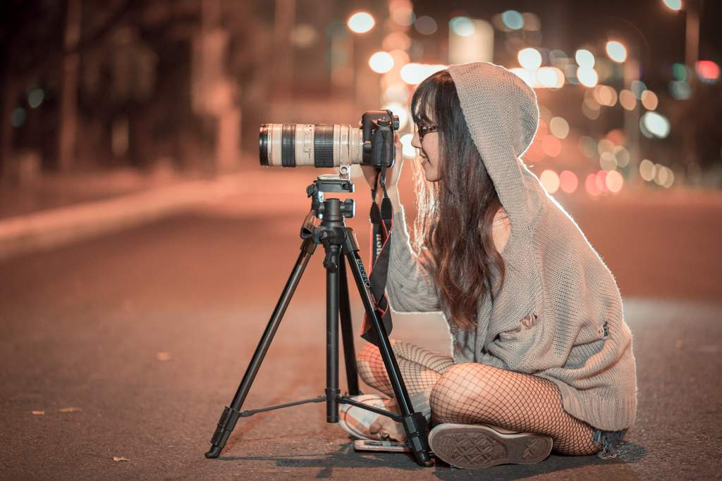 Woman sitting cross legged in middle of road at night, behind a professional-looking camera on small tripod
