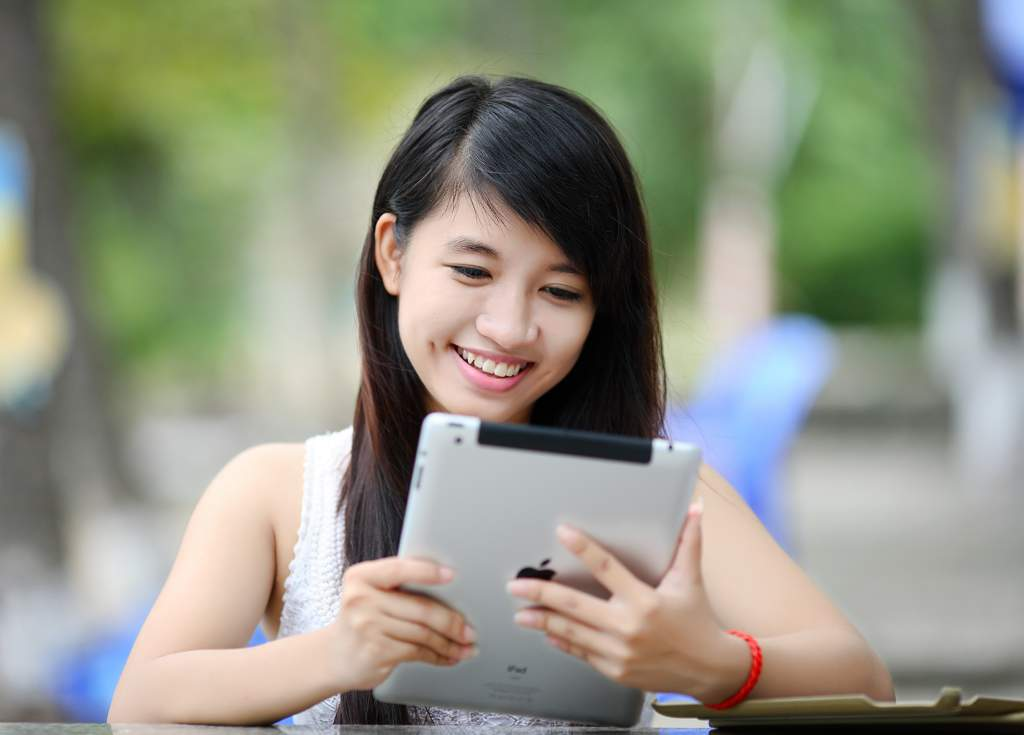 Woman with long dark hair looking at iPad and smiling.