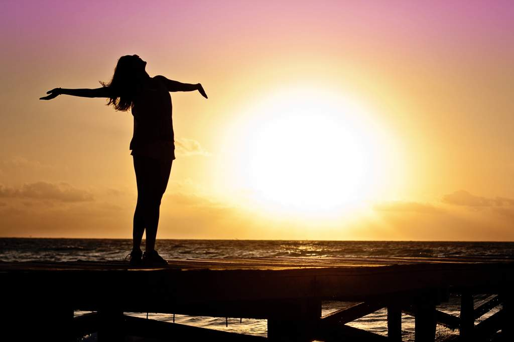 Silhouette of a woman standing on a pier stretching her arms out in front of the sunrise and the ocean.
