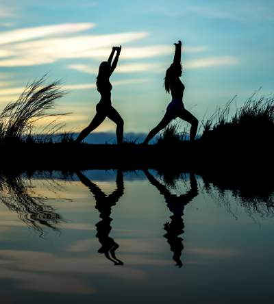 Silhouette of two women doing yoga or similar exercise as the sun rises. The scene is reflected in the water in front of them.