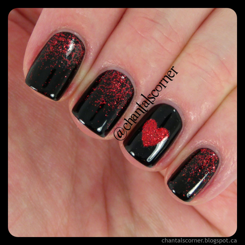 Black fingernails with fade of red sparkles. One nail has a red sparkly heart.