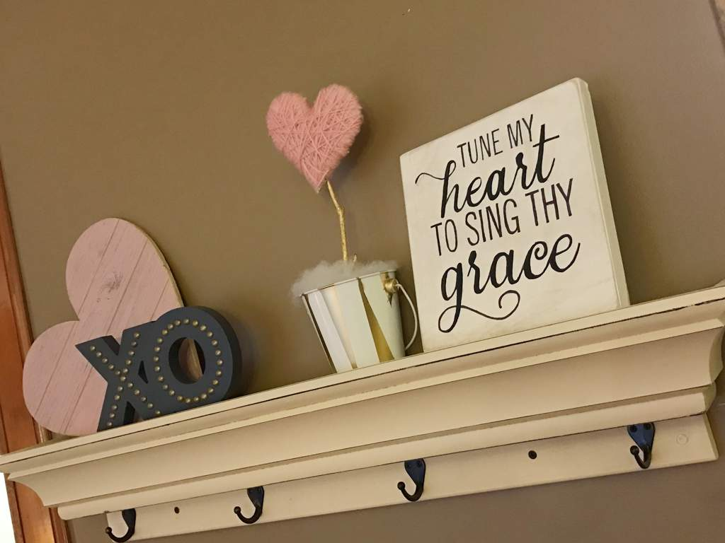 "A pink wound-yarn heart on a gold stem on a shelf next to a wooden heart, X and O, and a sign that says ""tune my heart to sing thy grace"""