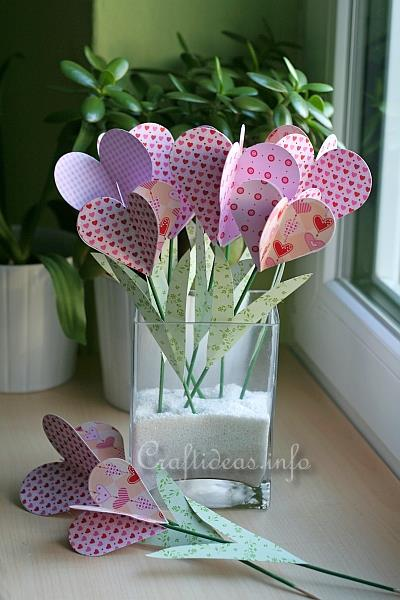 Bouquet of pink paper hearts with heart patterns with paper stems and leaves in a glass vase by a window.