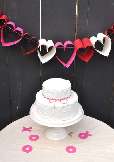A white two-layered cake with a pink ribbon below a chain of red, pink and white paper-chain hearts.