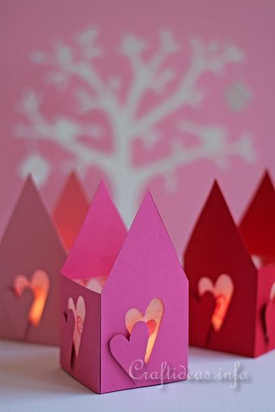 Red, purple and pink paper tealight holders with heart shapes cut out of the sides and pointed tops. There is a white paper tree in the background.