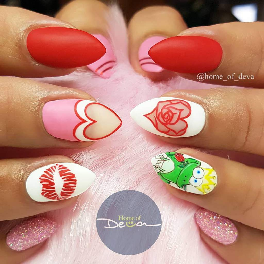 Woman's hands holding something pink and furry. Has valentines themed nail designs including red nails, a heart, lips, a frog prince and pink sparkly nails.