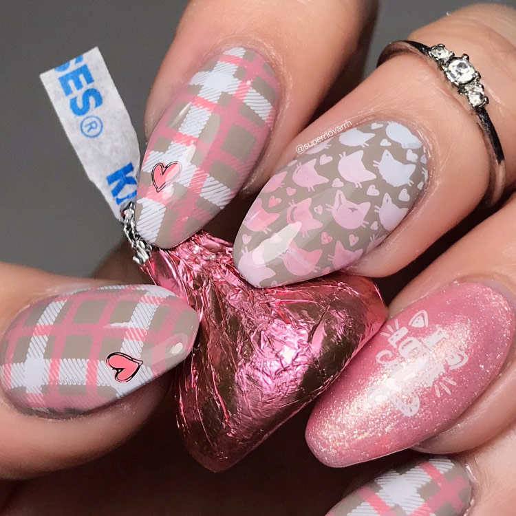 "Woman's hand holding a pink foil-wrapped ""kisses"" sweet. Three fingernails have a pink white and grey checked design, two have cat themed designs."