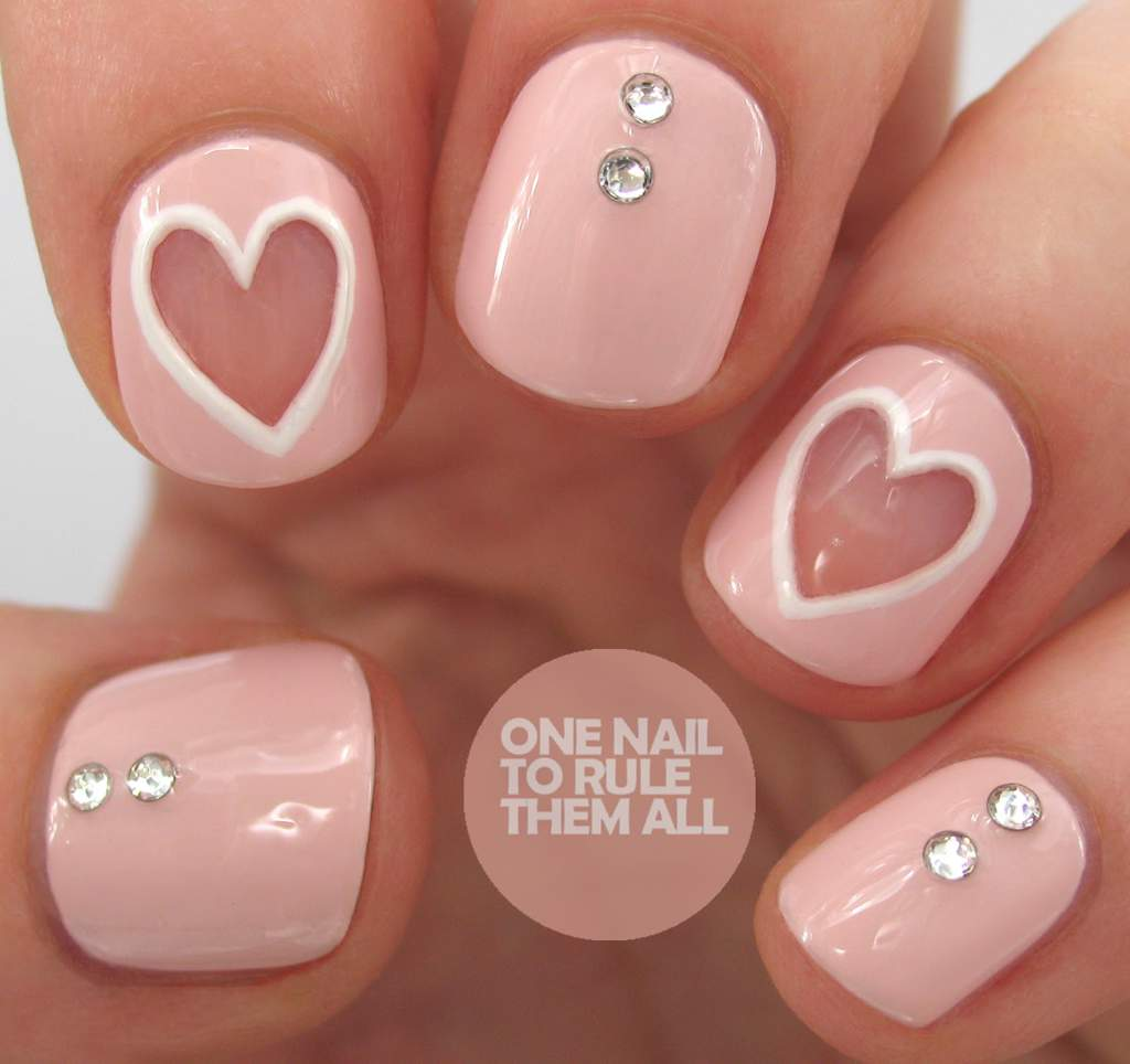 Pink fingernails - three have two crystals embedded, two have negative white outlined hearts.