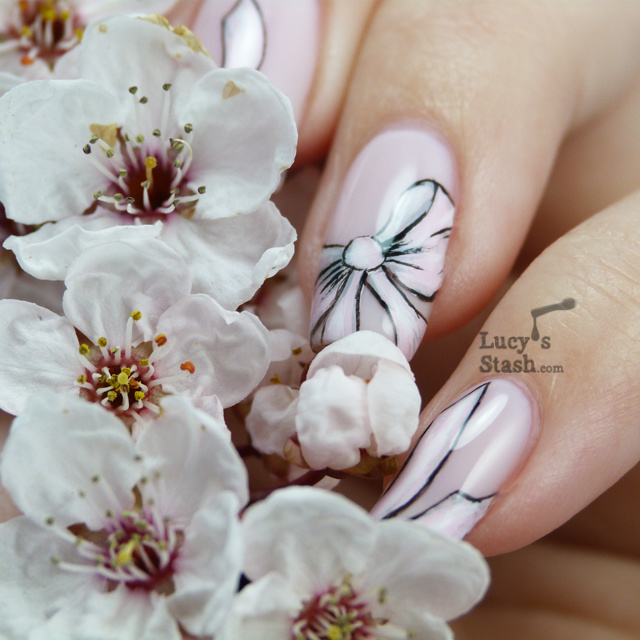 Woman's hand holding white blossom. She has long pink painted fingernails with pink bows outlined in black.