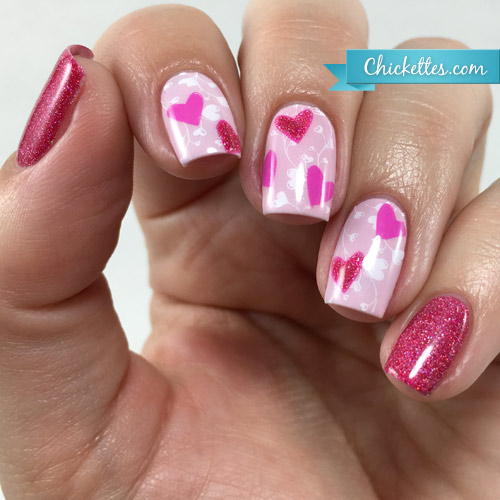 Woman's hand with three pink fingernails decorated with pink hearts, and two red sparkly fingernails.