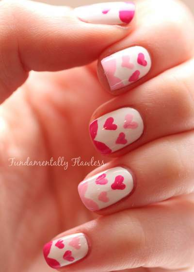 Hand with white fingernails with dark and light pink hearts on them.