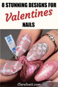 Woman's hand with fingernails in grey, pink and white plaid design with hearts and two cat designs. She is holding a Hershey's Kiss.