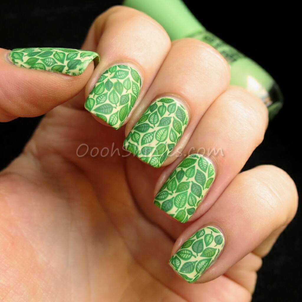 Painted fingernails with green leaves stamped on pale background.
