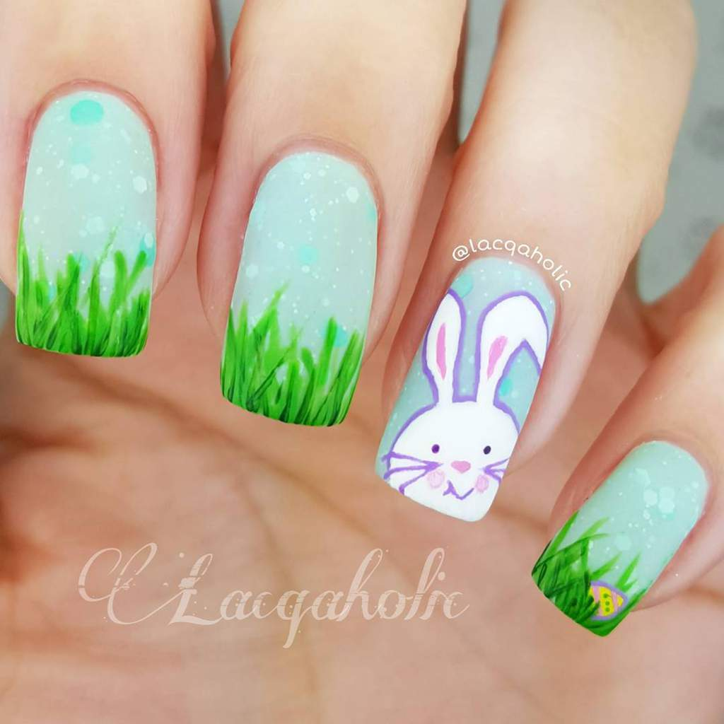 Painted fingernails - left hand two have a blue sky and green grass design - next one has a white Easter bunny outlined in lilac against a blue sky, and the right hand nail shows a small easter egg hidden in the grass under a blue sky.