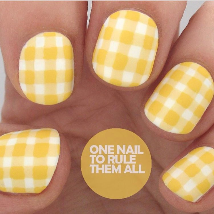 Bright yellow painted fingernails with white checks making a Gingham type pattern. Text overlay reads One Nail to Rule Them All.
