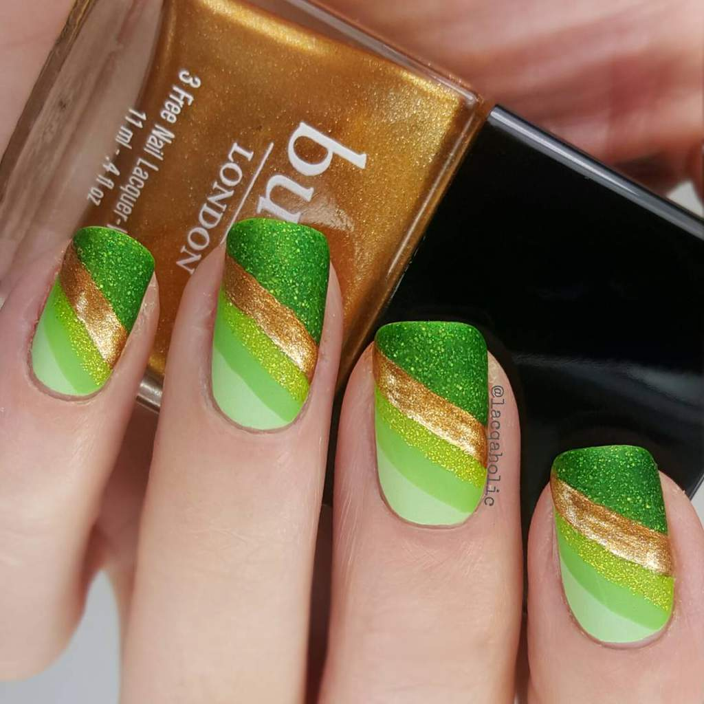 Fingernails with glittery green and gold diagonal striped design.